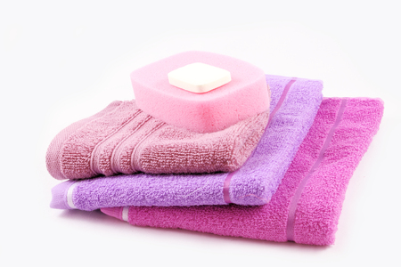 Soap, sponge and towels, isolated on white. Concept of personal hygiene and relaxation.