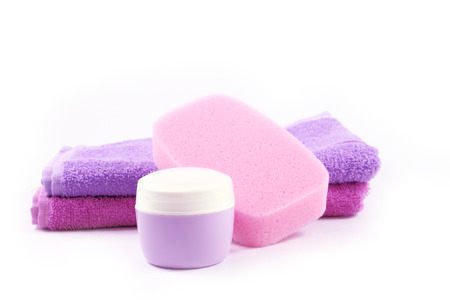 Container of cream, sponge and towels, closeup view. Concept of personal hygiene.