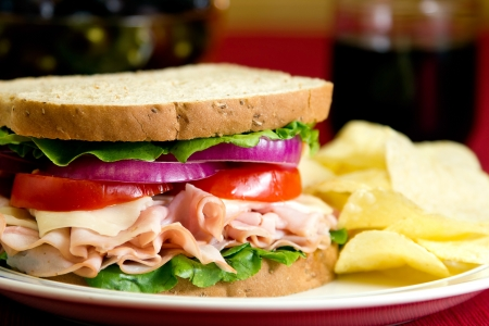 A healthy fresh turkey sandwich with turkey, swiss cheese, lettuce, tomato and onions.