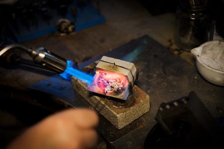 Foto de Jeweler melts with a flame silver or gold on old workbench in jewelers workshop - Imagen libre de derechos