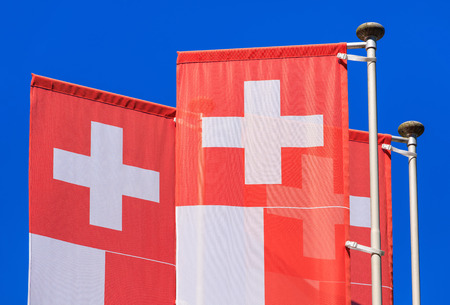 Flags of Switzerland against blue sky.