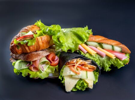 Photo pour A few sandwiches and rolls with cheese, salad, sausage and vegetables - image libre de droit