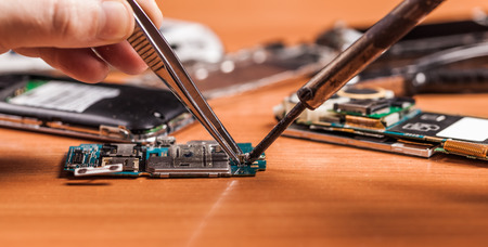 Photo pour employee repairing fractured phone on a wooden background - image libre de droit