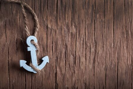 small anchor close-up on a wooden vintage background