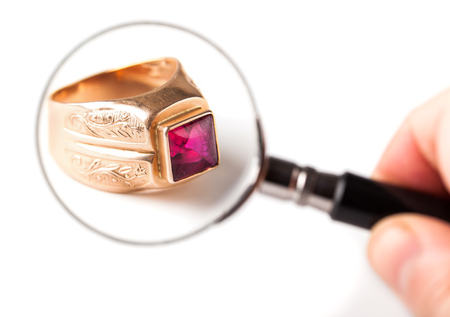 ancient gold ring with ruby on white background