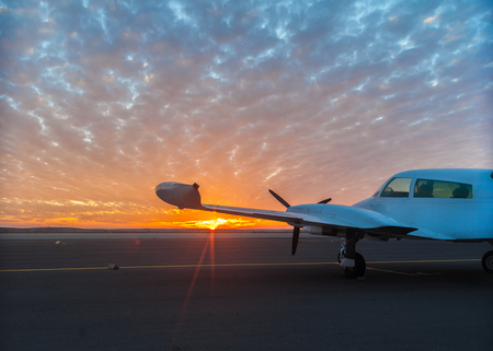 Photo pour small plane on the runway at sunset background - image libre de droit