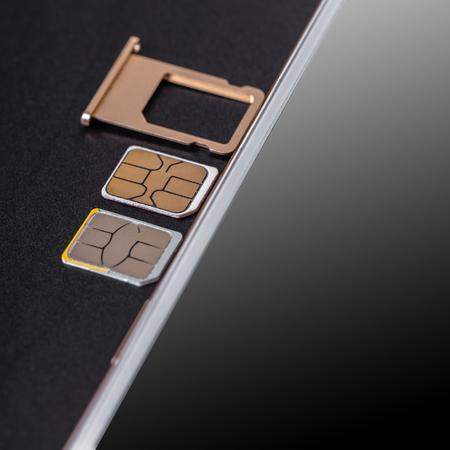 Photo pour mobile phone and sim card on a black background - image libre de droit
