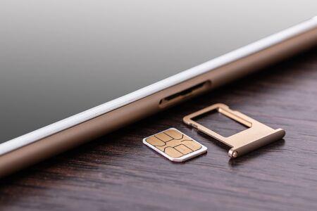 Photo pour mobile phone and sim card on a wooden background - image libre de droit