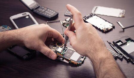 Photo pour mobile phone repair, hands closeup on a wooden table - image libre de droit