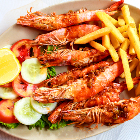 Plate grilled spicy prawn shrimps kebabs, vegetables, french fries with sauces and greens on light background.