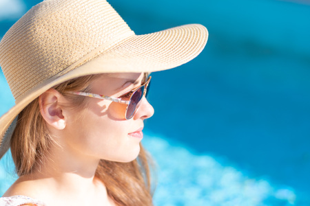 Summertime in pool. Young woman with floppy hat and sunglasses.