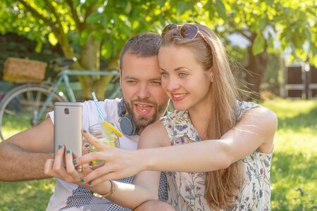 Summertime in garden. Young beautiful couple with cocktail taking selfie in garden.