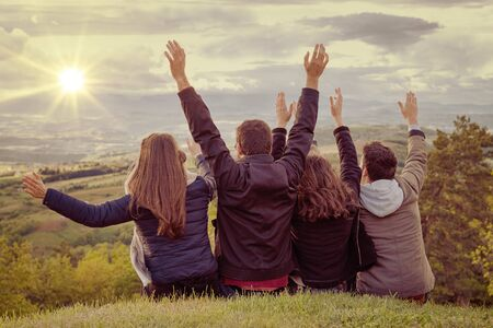 Photo pour Christian worship and praise. Group of friends hugging outdoors at sunset. - image libre de droit