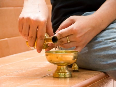 Pour water slowly onto a vessel as a sign of dedication of merit to the departed