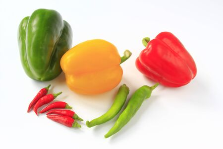 different peppers and chilis before white background
