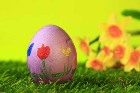 Easter decoration from single, colorful painted, Easter egg in green artificial grass