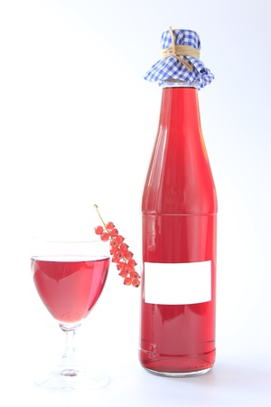 Fruit wine made from red currants with bottle and glass and one fruit against a white background