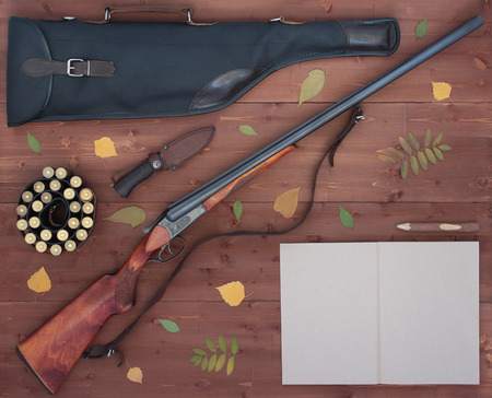 The gun, bandolier, knife, leather case for rifle and a notebook with a pencil. Wooden background. Flat lay concept. Top view.