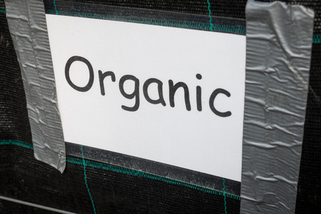 Sign from a garden centre reading organic, taped to a dark board.