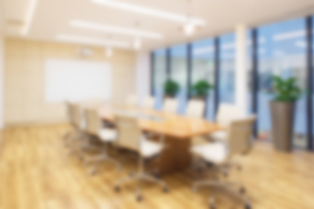 Foto de Defocused office background of a Board room with rustic wooden flooring,  meeting table and eames chairs. - Imagen libre de derechos