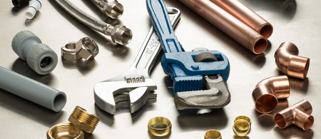 Photo pour Various plumbers tools and plumbing materials including copper pipe, elbow joint, wrench and spanner. shot on a bright stainless steel background. - image libre de droit