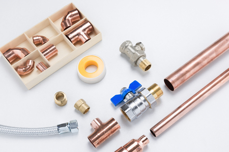 Copper pipes and joints, steel valve, and plumber's tape on white background
