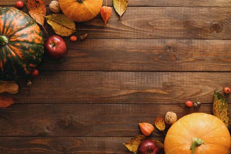 Photo pour Autumn frame made of pumpkins, dried fall leaves, apples, red berries, walnuts, blanket on wooden table. Thanksgiving, Halloween, Autumn Harvest concept. Flat lay composition, top view, copy space - image libre de droit