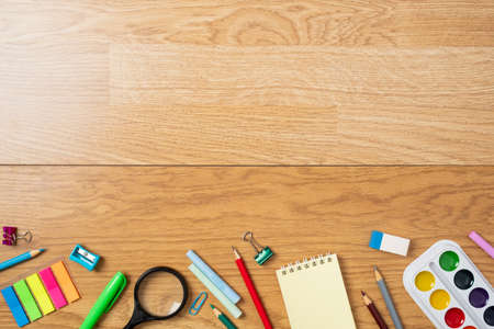Photo for Background with bottom border made of stationery, school supplies on wooden table. Education, studying and back to school concept. Child desk top view, copy space, flat lay composition. - Royalty Free Image