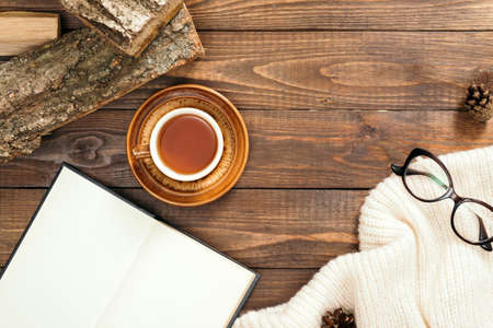 Photo pour Hygge style flatlay composition with cup of tea, book with empty pages, white knitted scarf, woman glasses, firewood on wooden desk table. Autumn or winter holidays concept. Flat lay, top view. - image libre de droit