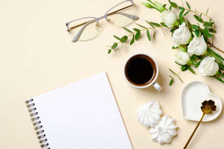 Photo pour Flat lay feminine accessories, glasses, blank paper notepad, coffee cup, marshmallow and white roses flowers on pastel colors beige background. Top view beauty blogger desk with diary and female stuff - image libre de droit