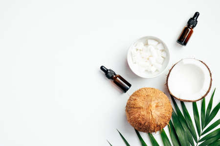 Foto de Natural coconut essential oil for hair care with palm leaf and coconuts on white background. SPA organic cosmetic, health and beauty concept. Flat lay, top view - Imagen libre de derechos