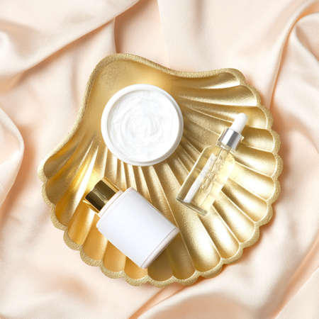 Photo pour Golden pearl shell decoration with set of cosmetics products. Flat lay, top view. - image libre de droit