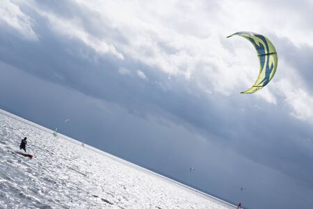 A lone kitesurfer floats in the sunshine on a wooden board with a kite on the silver water of the Baltic Sea of ?? Puck. Under the blue sky of Jastarnia in summer 2019.