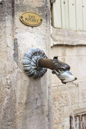 Bronze metal spout in an antique public fountain in Gigondas, vaucluse, France.