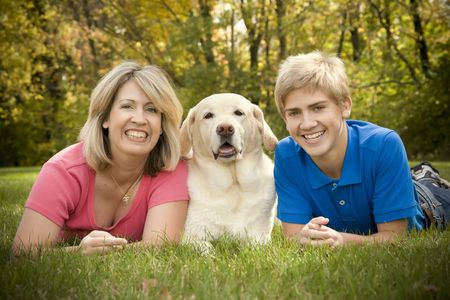 A mom and teenage son posing with their yellow lab