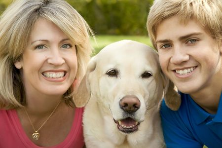 A mom and teenage son with their yellow labrador
