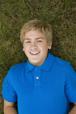 A blond teen in blue polo shirt lying in the grass