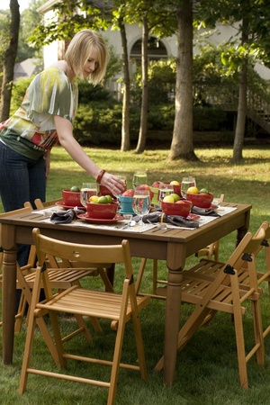 Woman Setting Table for Outdoor Dinner Party