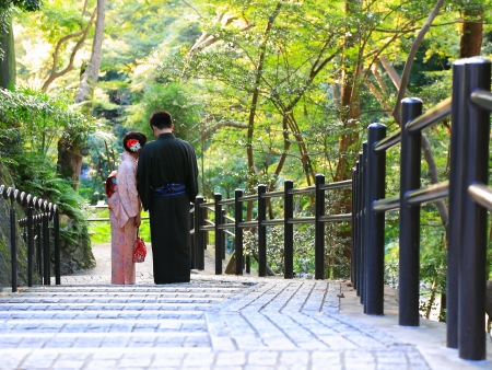 Japanese couple in traditional dress stand in the temple