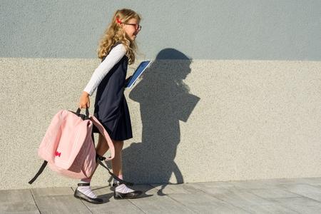 Photo pour  Schoolgirl with notebooks in hand. A girl with a backpack goes to school.  Back to school! - image libre de droit