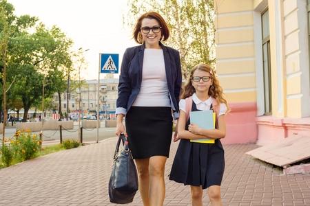 Photo pour Mother businesswoman takes the child to school. Urban style background - image libre de droit