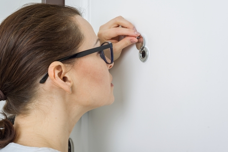 Photo pour Woman looks through the peephole of the front door in the apartment. - image libre de droit