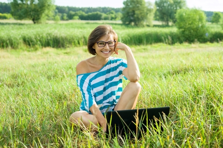 Foto de Outdoor portrait smiling middle-aged woman freelancer blogger traveler with laptop on nature. - Imagen libre de derechos
