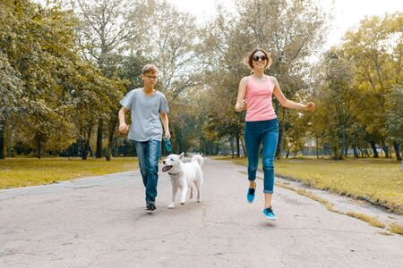 Photo pour Teenagers running with white dog Husky on the road in the park. - image libre de droit