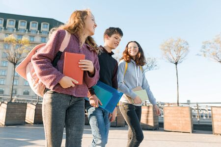 Photo pour Outdoor portrait of teenage students with backpacks walking and talking. City background, golden hour. - image libre de droit