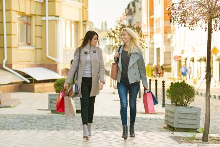 Photo for Two young smiling women on a city street with shopping bags, sunny autumn day. - Royalty Free Image