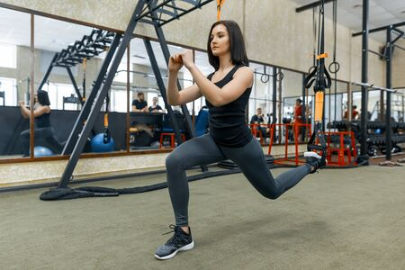 Young fitness woman doing exercises using the straps system in the gym. Sport, fitness, training, people concept