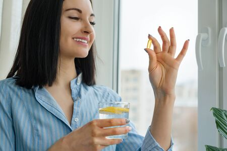 Photo pour Woman takes pill with omega-3 and holding glass of fresh water with lemon. Morning picture of house, near the window. Vitamin D, E, fish oil capsules. Nutrition, healthy eating, lifestyle. - image libre de droit