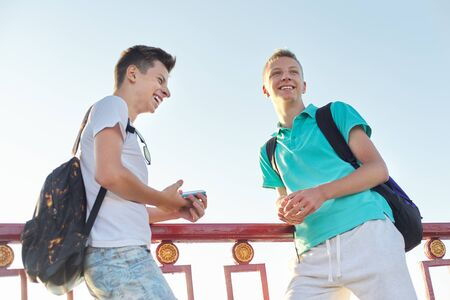 Photo pour Outdoor portrait of two talking boys teenagers 15, 16 years old, males laughing look at smartphone, golden hour - image libre de droit