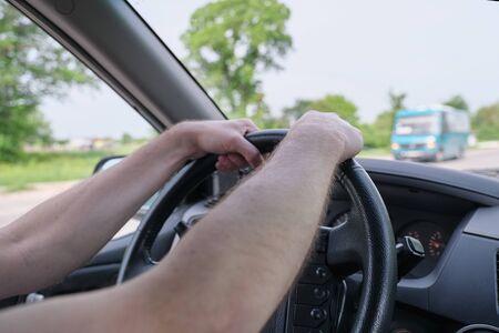 Photo pour Drivers men hands on steering wheel, day time - image libre de droit